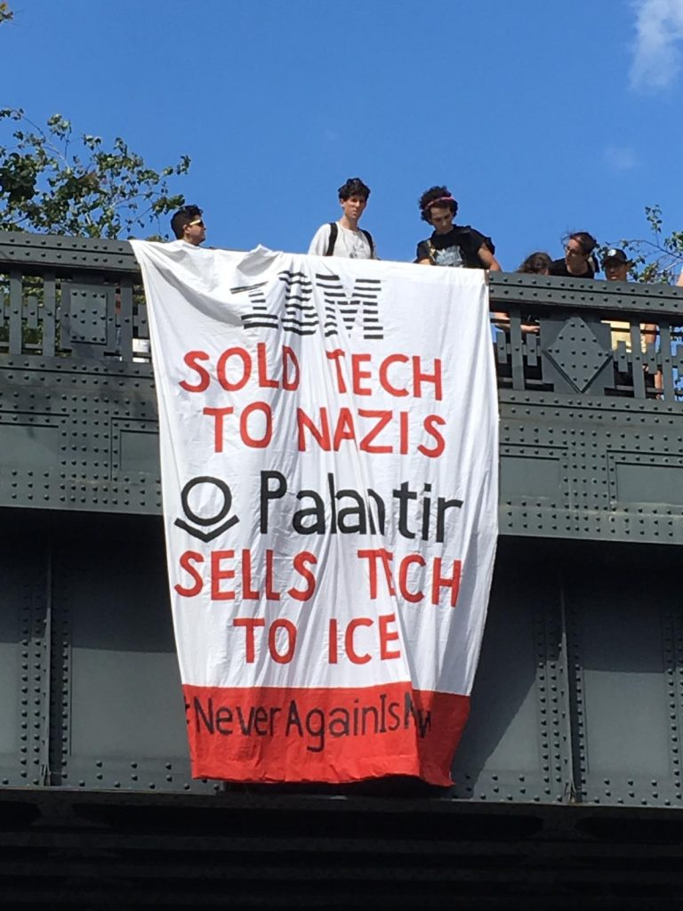 """Image of banner drop painted with the words """"IBM sold tech to Nazis; Palantir sells tech to ICE #NeverAgainISNow"""""""